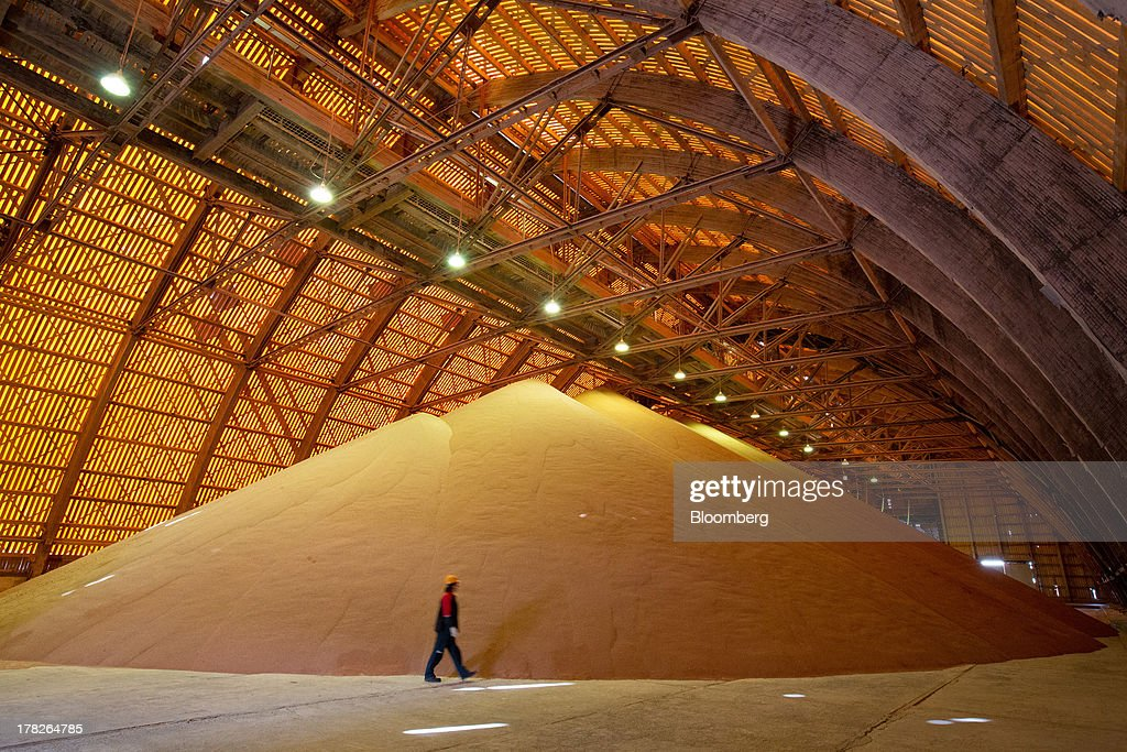 An employee passes a giant pile of potash grain inside a storage facility at the potash mine operated by OAO Uralkali in Berezniki, Russia, on Monday, Aug. 26, 2013. Russia pressured Belarus to free Vladislav Baumgertner, the head of OAO Uralkali, the world's biggest potash producer, saying a refusal may harm relations as the smaller nation faces a funding crunch. Photographer: Andrey Rudakov/Bloomberg via Getty Images