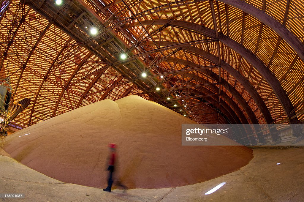 An employee passes a giant pile of potash standing in a storage facility operated by OAO Uralkali in Berezniki, Russia, on Monday, Aug. 26, 2013. Russia pressured Belarus to free Vladislav Baumgertner, the head of OAO Uralkali, the world's biggest potash producer, saying a refusal may harm relations as the smaller nation faces a funding crunch. Photographer: Andrey Rudakov/Bloomberg via Getty Images