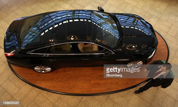 An employee passes a Jaguar XJ series automobile on display in an independent auto showroom in Moscow Russia on Friday Dec 28 2012 Tata Motors Ltd's...