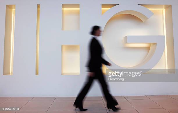 An employee passes a logo in the reception area of InterContinental Hotels Group Plc's headquarters in Denham UK on Friday July 22 2011...