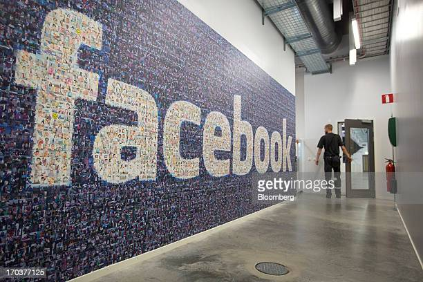 An employee passes a logo made from a collection of photographs on a wall inside Facebook Inc's new data storage center near the Arctic Circle in...