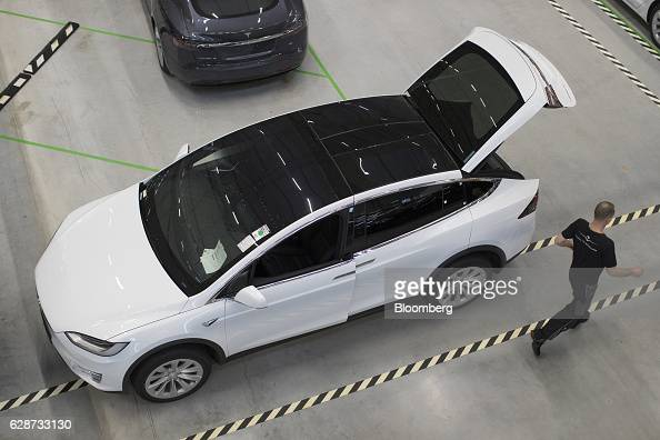 An employee passes a new Tesla Model X sports utility vehicle following assembly for the European market at the Tesla Motors Inc factory in Tilburg...