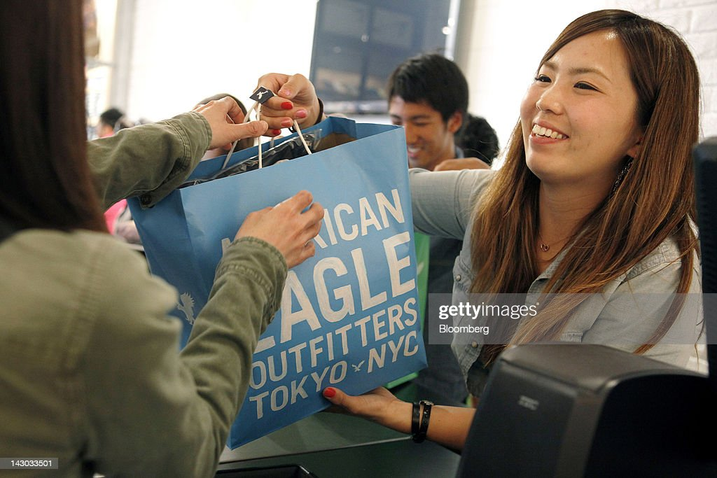 An employee passes a shopping bag to a customer at the checkout counter of an American Eagle Outfitters Inc. store in Tokyo, Japan, on Wednesday, April 18, 2012. American Eagle Outfitters Inc., a retailer of men's and women's casual apparel, opened its first store in Japan inside the Tokyu Plaza Omotesando Harajuku retail complex in the Omotesando district of Tokyo today. Photographer: Kiyoshi Ota/Bloomberg via Getty Images