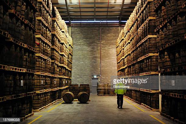 An employee passes American oak barrels containing Jameson whiskey produced by Irish Distillers Ltd at the PernodRicard SA distillery in Middleton...