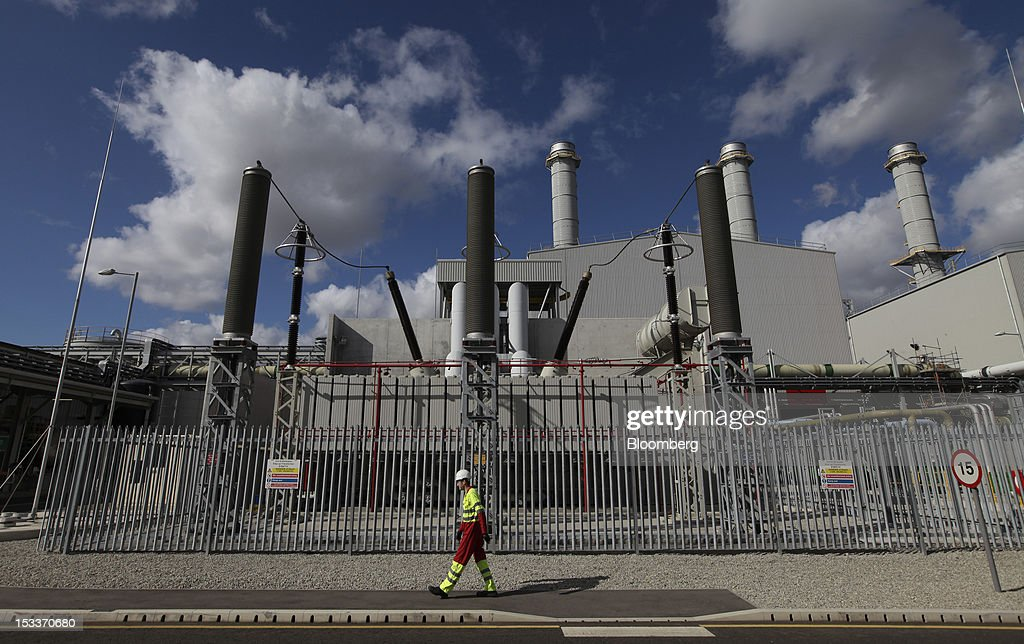 An employee passes an electricity transmission substation at the EON AG gas fired power station on the Isle of Grain, U.K., on Thursday, Oct. 4, 2012. The National Grid Plc and E.ON have worked together to link two plants with twin pipelines, allowing surplus heat from electricity generation at E.ON.s power station to heat LNG and convert it back to gas. Photographer: Chris Ratcliffe/Bloomberg via Getty Images