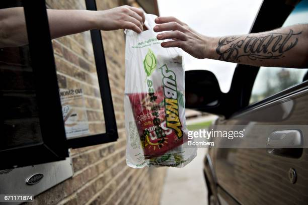 An employee passes an order to a customer at the drivethru of a Subway Restaurants location in Princeton Illinois US on Thursday April 20 2017 Subway...