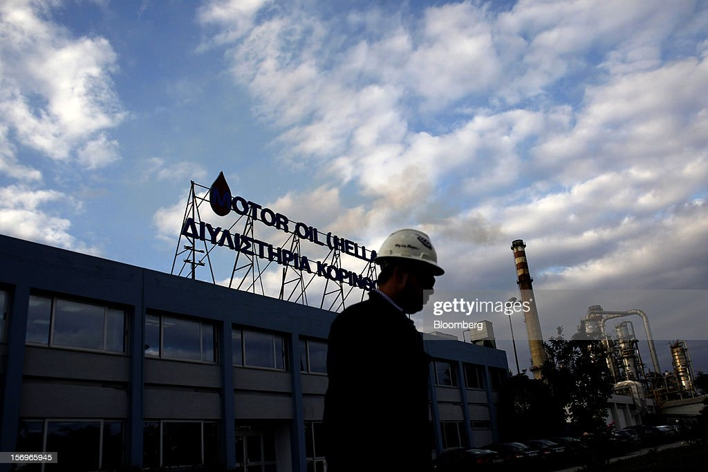 An employee passes beneath a Motor Oil Hellas sign above a building at the company's oil refinery in Agioi Theodoroi, Greece, on Friday, Nov. 23, 2012. Motor Oil Hellas SA Chief Financial Officer Petros Tzanetakis said Greek companies face difficulties in securing financing as foreign banks look at Greece with a 'skeptical eye.' Photographer: Kostas Tsironis/Bloomberg via Getty Images
