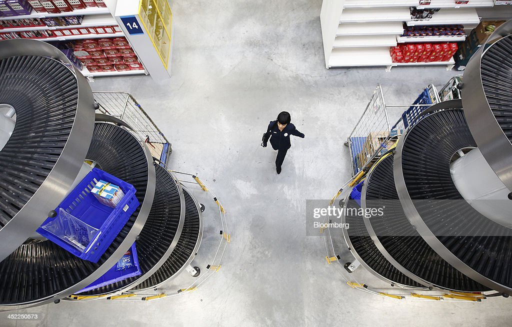 An employee passes between spiral grocery delivery shafts at a Tesco Plc on-line distribution center, in Erith, U.K., on Wednesday, Nov. 27, 2013. Tesco Plc, the U.K.'s largest retailer, will sell land near some of its Polish hypermarkets to attract additional services around those stores. Photographer: Simon Dawson/Bloomberg via Getty Images