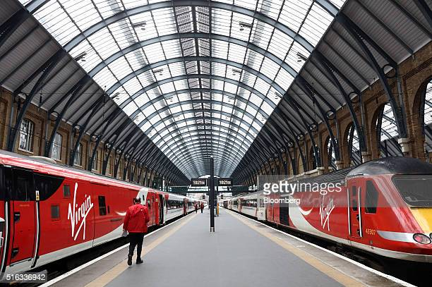 An employee passes between two high speed Virgin trains at Kings Cross station in London UK on Friday March 18 2016 Virgin Trains will revive plans...