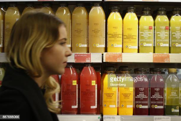 An employee passes bottles of fresh fruit juices in the foodhall inside a branch of Marks Spencer Group Plc in London UK on Tuesday Dec 5 2017 Brexit...