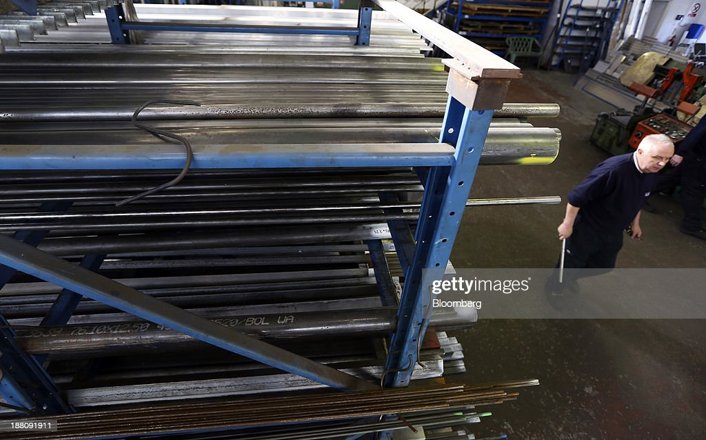 An employee passes lengths of metal stored on racks in the warehouse at Metal Supermarkets in Southampton, U.K., on Friday, Nov. 15, 2013. The Bank of England sees gross domestic product rising 0.9 percent this quarter before easing in the early part of 2014, according to its new projections. Photographer: Chris Ratcliffe/Bloomberg via Getty Images