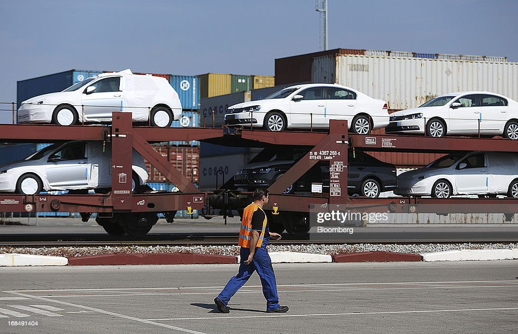 An employee passes new Volkswagen AG automobiles on a rail transporter at the port of Koper, operated by Luka Koper d.d., in Koper, Slovenia, on Thursday, May 9, 2013. The former Yugoslav nation, mired in its second recession since 2009, will contract this year and next, according to a May 3 report by the European Commission. Photographer: Chris Ratcliffe/Bloomberg via Getty Images