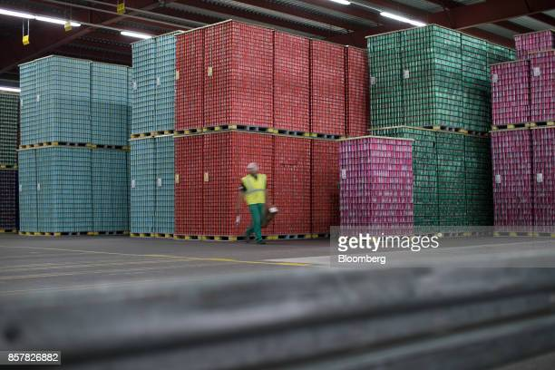 An employee passes pallets stacked with softdrink cans ahead of shipping at the Refresco Group NV beverage bottling factory in Maarheeze Netherlands...