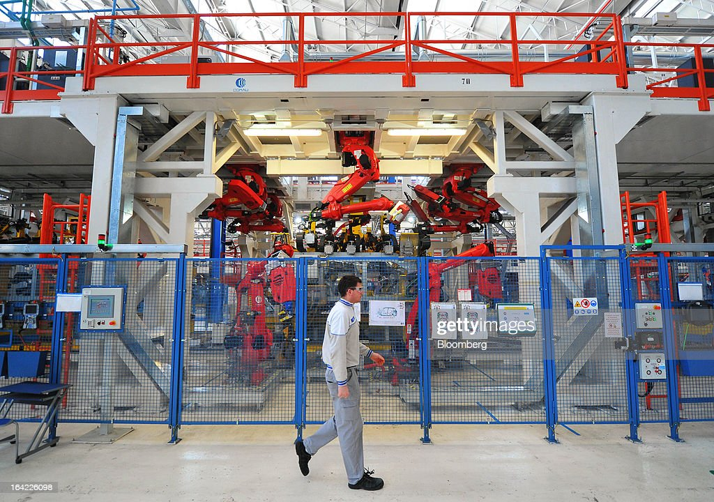 An employee passes robotic machines used for the assembly of Fiat 500L automobiles at the Fiat Automobili Srbija plant in Kragujevac, Serbia, on Wednesday, March 20, 2013. Fiat Automobili Srbija, a joint venture between the government and Italian carmaker Fiat, is Serbia's sole automaker. Photographer: Oliver Bunic/Bloomberg via Getty Images