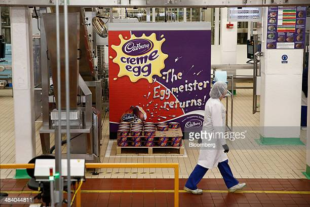 An employee passes spools of foil used for wrapping Cadbury Creme Eggs in the Bournville Cadbury factory operated by Mondelez International Inc in...