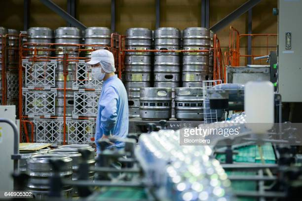 An employee pauses while moving kegs of YoHo Brewing Co brand beers on the production line at the company's brewery in Saku Nagano Prefecture Japan...