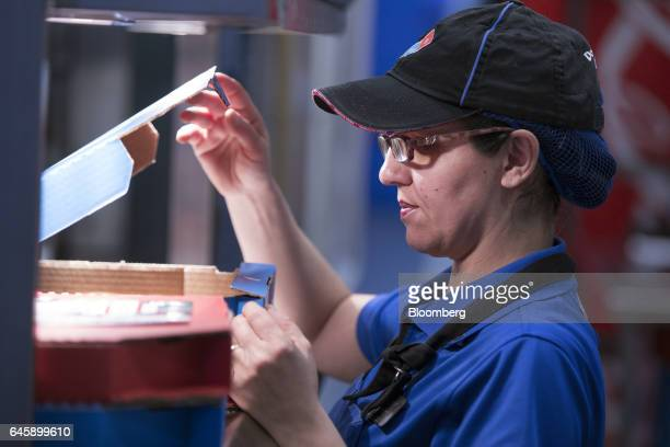 An employee performs a quality check on a pizza ahead of delivery inside a Domino's Pizza Group Plc store in Hanwell London UK on Monday Feb 27 2017...