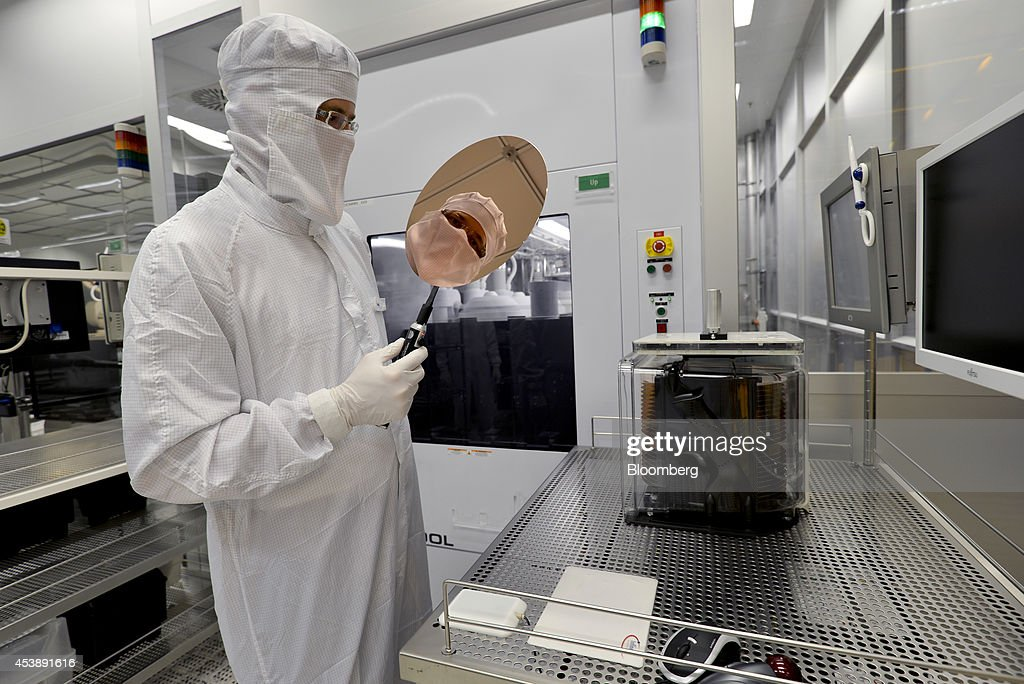 An employee performs a quality control check on an Infineon Technologies AG semiconductor wafer in this arranged photograph in a sterile room at the company's factory in Regensburg, Germany, on Tuesday, Jan. 29, 2013. Infineon Technologies AG, Germanys largest chipmaker, agreed to buy International Rectifier Corp. for about $3 billion in cash, adding to its power-management technology business. Photographer: Guenter Schiffmann/Bloomberg via Getty Images