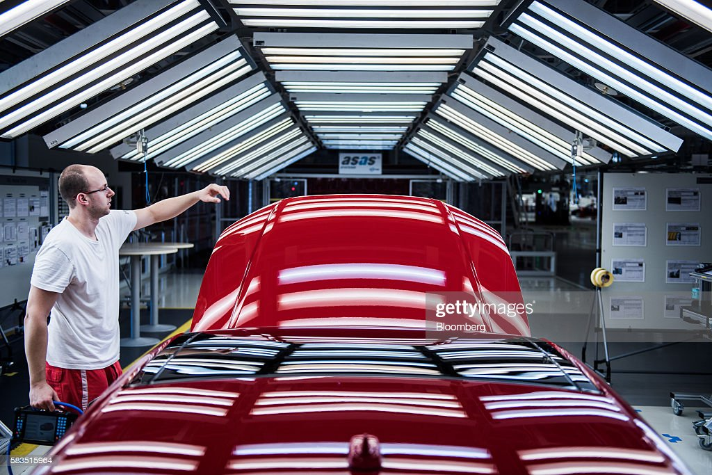 An employee performs a quality control check on the hood of an Audi automobile inside the Audi AG production plant in Gyor Hungary on Monday July 25...