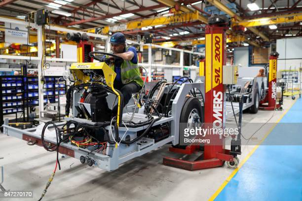 An employee performs electrical tests on the dashboard of an Enviro 400 bus under construction at the Alexander Dennis Ltd factory in Guildford UK on...