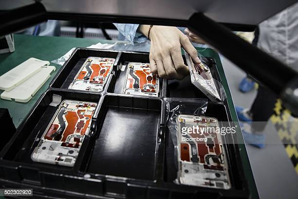 An employee picks up a OnePlus X smartphone on the assembly line at the OnePlus manufacturing facility in Dongguan China on Thursday Dec 17 2015...