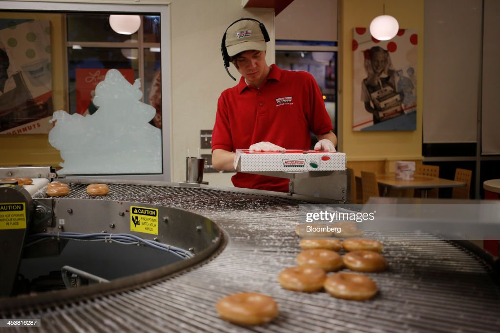 An employee picks up fresh donuts from a conveyor belt at a Krispy Kreme Doughnuts Inc. store in Farragut, Tennessee, U.S., on Wednesday, Dec. 5, 2013. The doughnut chain plans to add at least 30 new U.S. stores next year and is opening up new markets for franchising. Photographer: Luke Sharrett/Bloomberg via Getty Images