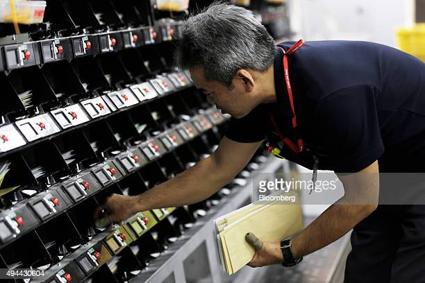 An employee picks up mail from a sorting machine at a Japan Post Co post office in Tokyo Japan on Monday Oct 26 2015 Japan Post Holdings and its...