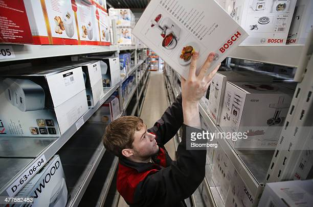 An employee place a Robert Bosch GmbH electronic product on a shelf in the goods warehouse inside a fulfilment center operated by Ulmart Russia's...