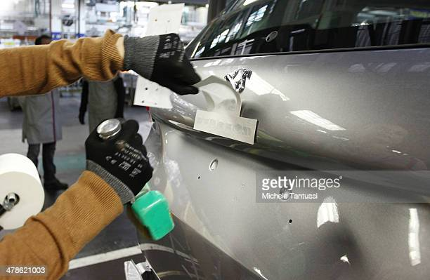 An employee places a badge onto the trunk of a Peugeot 2008 SUVs at the PSA Peugeot Citroen assembly plant on March 14 2014 in Mulhouse France...