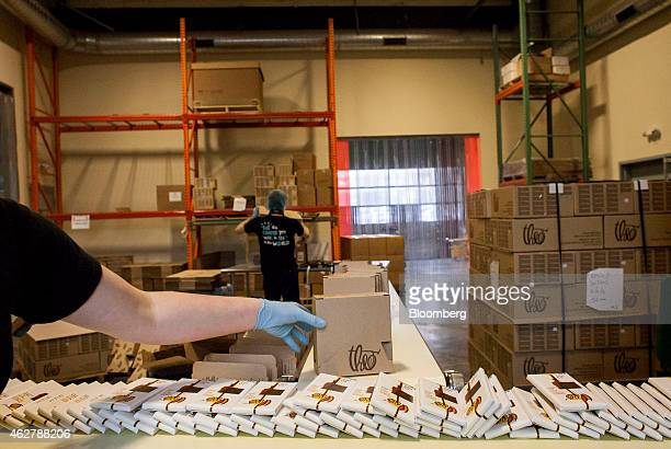 An employee places a box of chocolate bars onto a conveyor belt for shipping at the Theo Chocolate factory in Seattle Washington US on Monday Feb 2...
