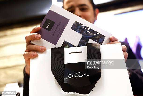 An employee places a box of chocolates into a customer bag inside a branch of Hotel Chocolat Ltd in London UK on Wednesday March 23 2016 Hotel...