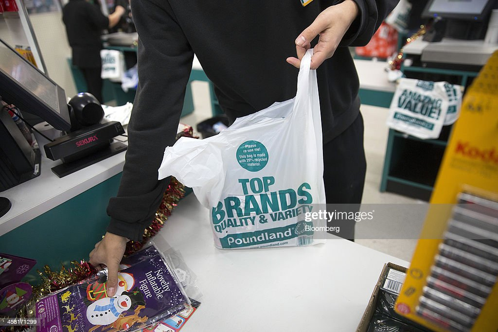 An employee places a customer's goods into a branded plastic shopping bag at a check-out desk inside a Poundland discount store, operated by Poundland Holdings Ltd., in Birmingham, U.K., on Friday, Dec. 20, 2013. U.K. discount retailer Poundland has hired Rothschild to manage its IPO, according to the Sunday Times newspaper. Photographer: Simon Dawson/Bloomberg via Getty Images