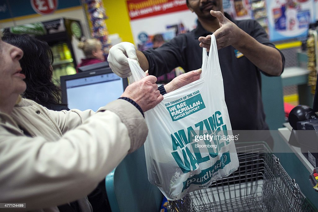 An employee places a customer's goods into a branded plastic shopping bag at a check-out desk inside a Poundland discount store, operated by Poundland Group Plc in London, U.K., on Friday, March 7, 2014. Poundland Group Plc has demand for all the shares it is selling in an initial public offering that will value the U.K. discount retailer at as much as 750 million pounds ($1.3 billion), according to terms of the deal. Photographer: Simon Dawson/Bloomberg via Getty Images