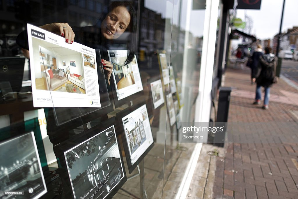 An employee places a 'For Sale' advert in the window display board of a Clapham estate agent's, in this arranged photograph in London, U.K., on Friday, Nov. 23, 2012. U.K. mortgage approvals rose to a nine-month high in October, the British Bankers' Association said. Photographer: Simon Dawson/Bloomberg via Getty Images