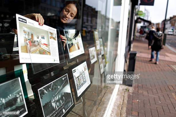 An employee places a 'For Sale' advert in the window display board of a Clapham estate agent's in this arranged photograph in London UK on Friday Nov...