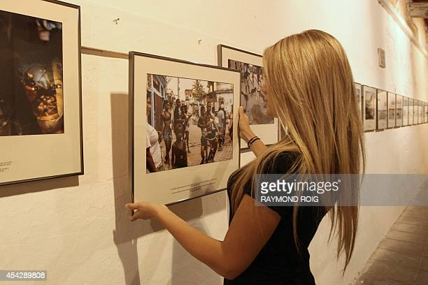 An employee places a framed photo on a wall before the opening of the exhibition 'Football as seen through the eyes of children in Cidade de Deus...