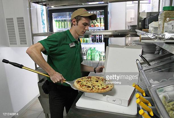 An employee places a freshlybaked pizza in a box at a Papa John's International Inc pizza restaurant in Moscow Russia on Tuesday Aug 16 2011 Domino's...
