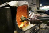 An employee places a gold bar in a furnace on April 6 2009 at a plant of gold refiner and producer ArgorHeraeus in Mendrisio in the southern Swiss...
