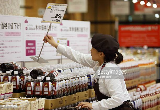 An employee places a new price sign on bottles of coffee ahead of consumption tax hike at an Aeon Co supermarket in Chiba Japan on Monday March 31...
