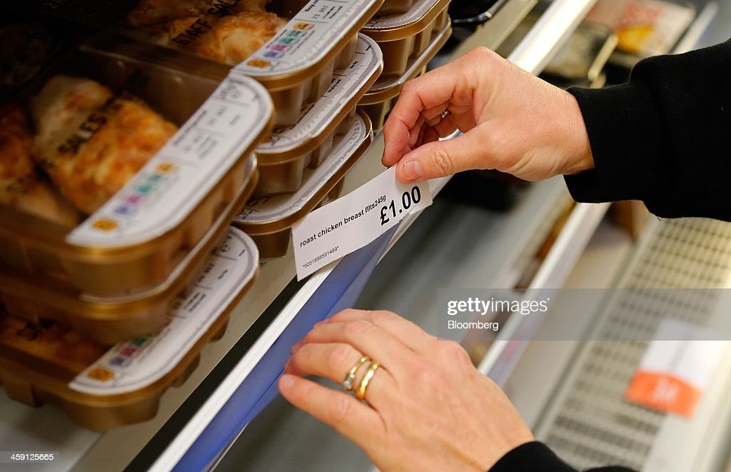 An employee places a one pound price tag for chicken in the chilled meat section inside the Community shop, a supermarket for low-income families, in Goldthorpe, U.K., on Monday, Dec. 23, 2013. Company Shop Ltd. created the Community shop for people in, or bordering on, food poverty, selling surplus goods from major retailers at discounted prices. Photographer: Paul Thomas/Bloomberg via Getty Images