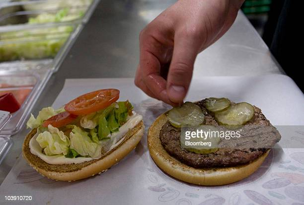 An employee places a pickle in a whopper burger at a Burger King restaurant in Basildon UK on Wednesday Sept 8 2010 Burger King Holdings Inc agreed...