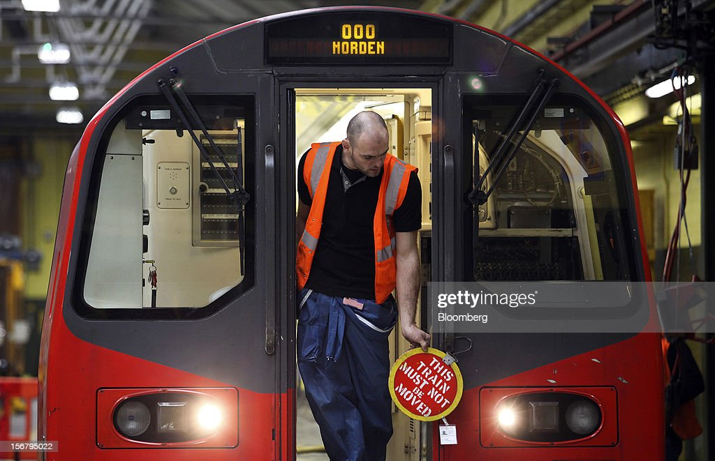 An employee places a safety sign on to the front a London Underground Northern Line train at Alstom SA's Traincare Centre in the Golders Green district of London, U.K., on Wednesday, Nov. 21, 2012. Transport for London (TFL), who oversee the U.K. capital's public transport system, issued 300 million pounds ($476 million) of bonds five months ahead of schedule to take advantage of investor demand as it continues its 35 billion-pound transport investment program. Photographer: Chris Ratcliffe/Bloomberg via Getty Images
