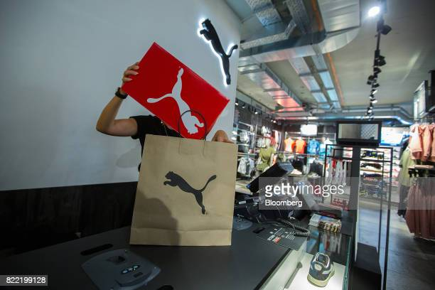 An employee places a shoebox into a branded paper bag inside a Puma SE sportswear clothing store in Berlin Germany on Tuesday July 25 2017 Puma...