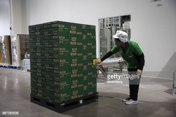An employee places a sticker on a pallet of Carabao energy drink at the Carabao Group Pcl plant in Chachoengsao Chachoengsao Province Thailand on...