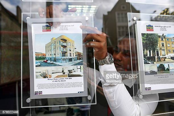 An employee places an advertisement for a house for sale into an estate agent's window in this arranged photograph in the Hackney borough of London...