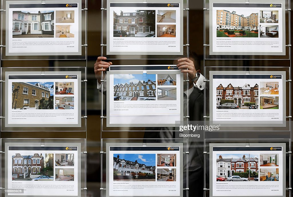 An employee places an advertisement for a rental apartment in the window display of a Clapham estate agents, in London, U.K., on Friday, Nov. 23, 2012. U.K. mortgage approvals rose to a nine-month high in October, the British Bankers' Association said. Photographer: Simon Dawson/Bloomberg via Getty Images
