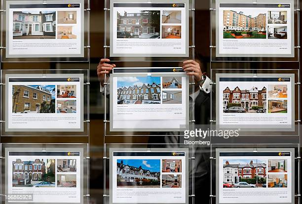 An employee places an advertisement for a rental apartment in the window display of a Clapham estate agents in London UK on Friday Nov 23 2012 UK...