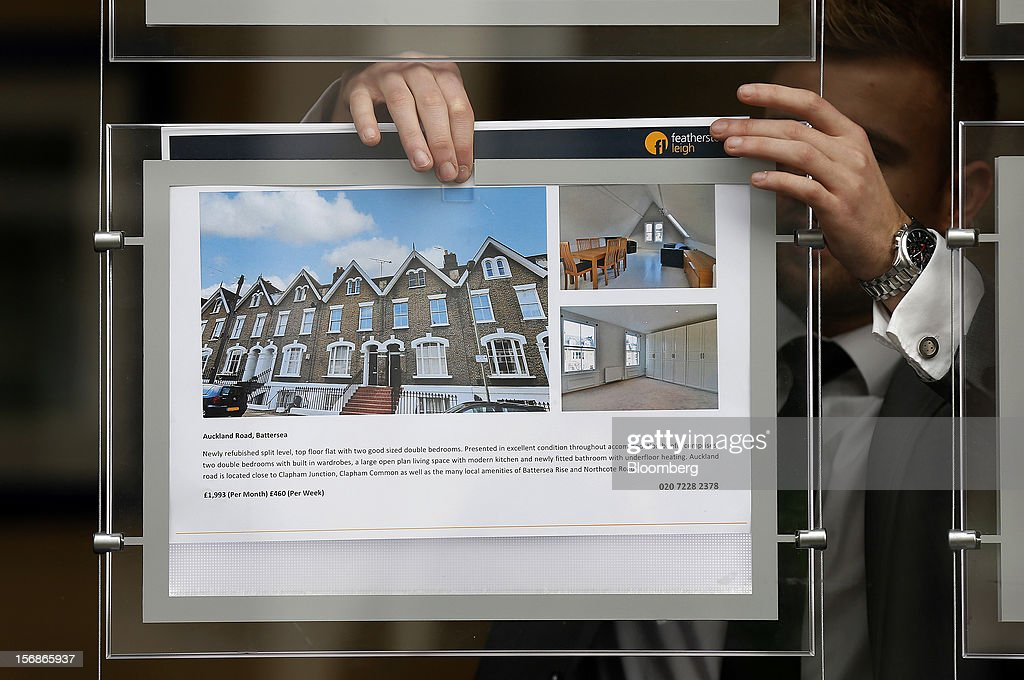 An employee places an advertisement for a rental apartment in the window display board of a Clapham estate agents, in London, U.K., on Friday, Nov. 23, 2012. U.K. mortgage approvals rose to a nine-month high in October, the British Bankers' Association said. Photographer: Simon Dawson/Bloomberg via Getty Images