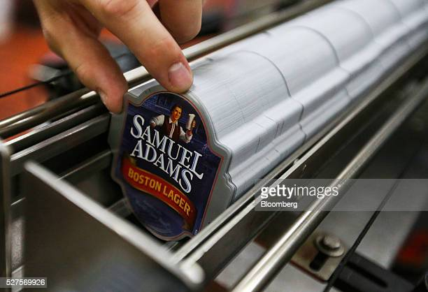 An employee places bottle stickers for Samuel Adams Boston Lager into a dispensing tray on the production line at the Shepherd Neame Plc brewery in...
