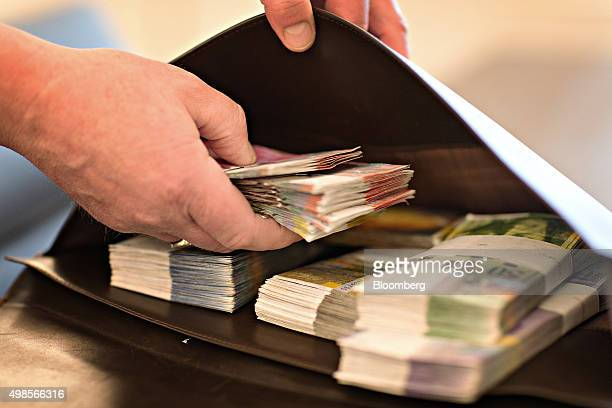 An employee places bundles of Swiss franc banknotes into a bag in the office of a bank in this arranged photograph in Zurich Switzerland on Friday...